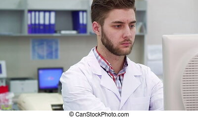 Male scientist works at the laboratory - Attractive male...