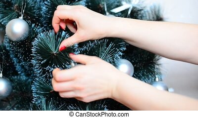 Woman decorate artificial Christmas tree with balls and bows...