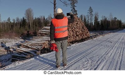Lumberjack with chainsaw take pictures on smart phone