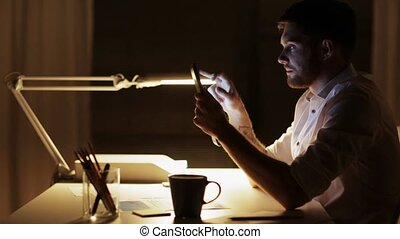man with tablet pc working late night at office - business,...