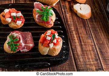 Set of bruschetta on black grill pan  wooden background. Tasty antipasto.