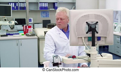 Male scientist looks to the side at the laboratory - Aged...