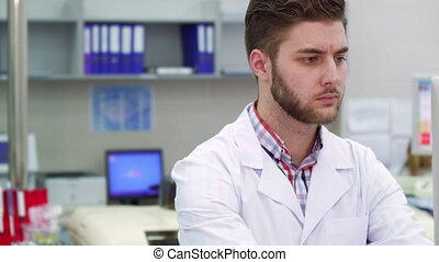 Man uses computer at the laboratory - Handsome caucasian man...