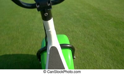 Scooter riding on grass. Handlebars and nature background....