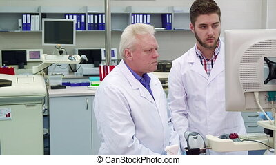 Two men look at the monitor at the laboratory - Two men in...
