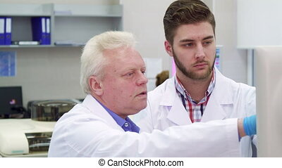 Man points his hand on monitor at the laboratory - Senior...