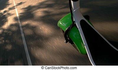 Fat wheel scooter moving. Asphalt road under sunlight....
