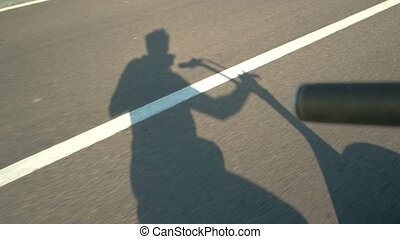 Shadows on asphalt road. Man riding motor scooter. Ride into...