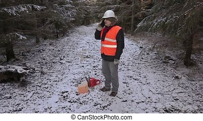 Lumberjack with phone, chainsaw and petrol can in forest