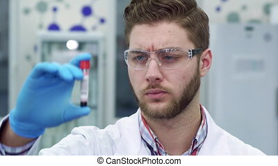 Man looking at the test-tube at the laboratory - Young...