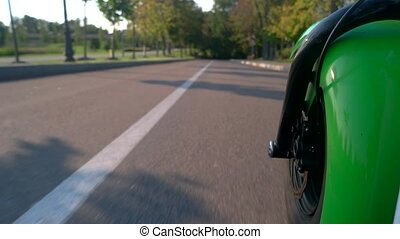 Motorcycle wheel and asphalt. Road in the park. New electric...