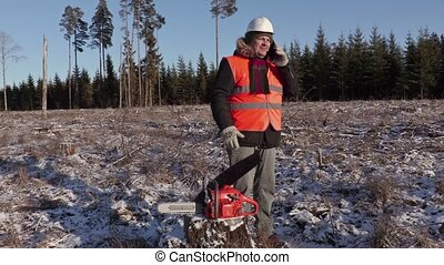 Lumberjack near chainsaw talking on smart phone in forest