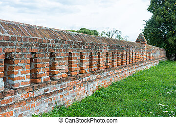 Wall of red brick. - Wall of red brick against the green...