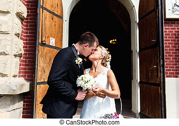 Groom kisses a bride with flower basket standing in the...