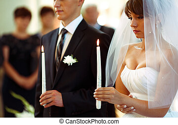 Wedding couple looks thoughtful holding candles during the ceremony in church