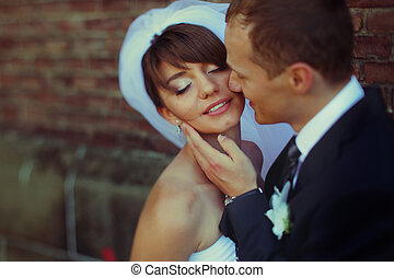 Bride smiles with closed eyes while groom touches her face...