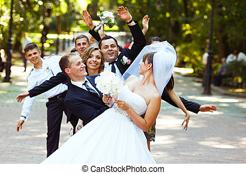 Bride looks over shoulder on friends while they hide behind her in park