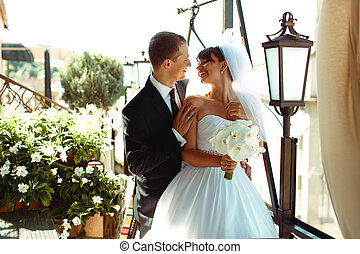Bride and groom smile looking at each other while they stand in a restaurant