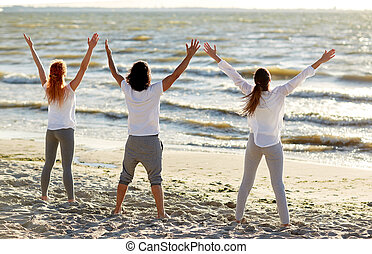 group of people making yoga or meditating on beach -...