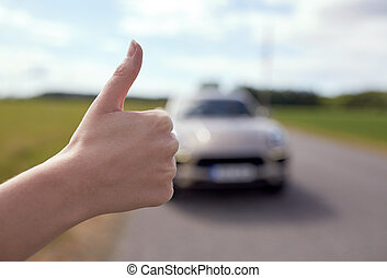 hitchhiker stopping car with thumbs up hand sign - road...