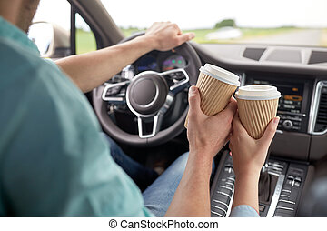 close up of couple driving in car with coffee cups - travel,...