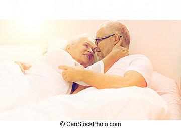 happy senior coupler lying in bad at home - family, bedtime,...