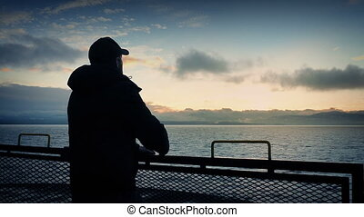 Man Looks From Back Of Ship At Sunset