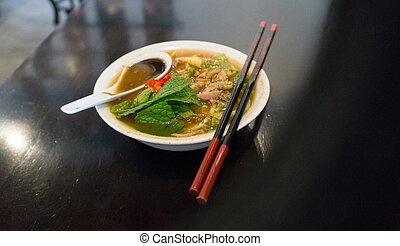 Delicious Asam Laksa with a red pair of chopsticks in...