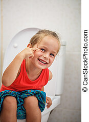 Boy sitting on the toilet - Boy in red shirt is sitting on...