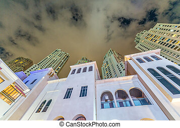 Night street view of old and modern Dubai Marina buildings - UAE