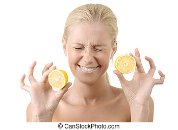 Beautiful young girl holding a sour lemon isolated