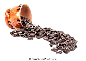 sunflower seeds spill out of wooden barrels on white...