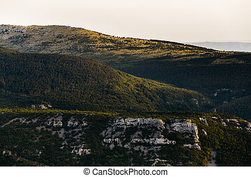 View of the hillside with rocks, forest in the rays of the setting sun in Croatia, Europe