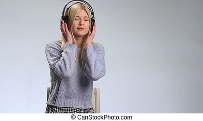 Dreamy teenage girl with headphones singing song over white....