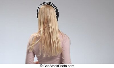 Happy smiling girl listening music in headphones
