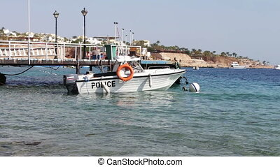Boat of water police standing in the sea near the pier on...