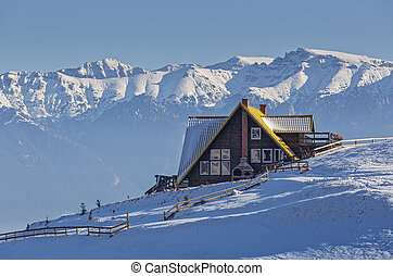 Alpine winter scenery with rustic chalet