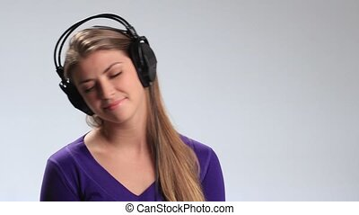 Attractive girl listening to music headphones - Beautiful...