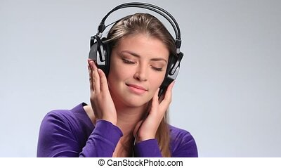 Lovely young woman listening music in headphones