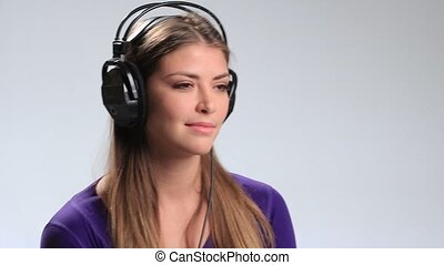 Cute smiling girl listening to music on headphones -...