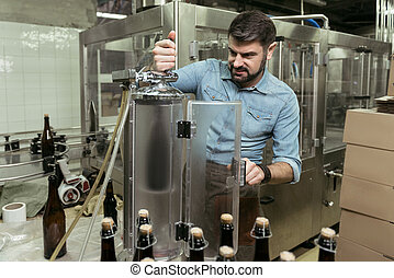 Concentrated man working hard in brewery