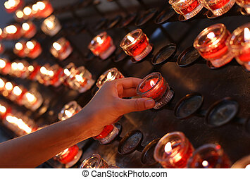 red candles lighted and the hand of the child - many red...