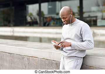 Attractive black man listening to music with headphones in...