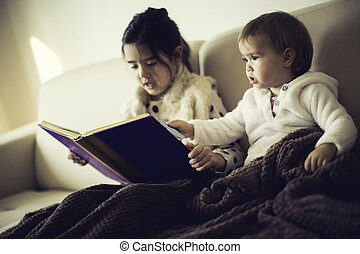 Cute little sisters reading a book in the bed