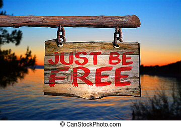 Just be free motivational phrase sign on old wood with...