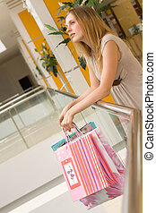 attractive young woman with bags in shopping centre