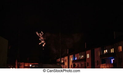 fireworks in the night sky over houses