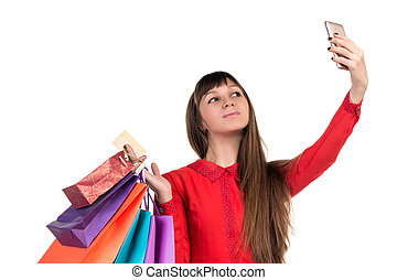 Young woman shopping with credit card holding packages doing selfie