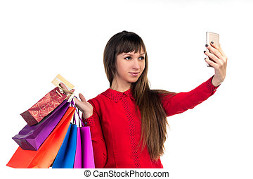 Young woman shops with credit card holding bags oing selfie