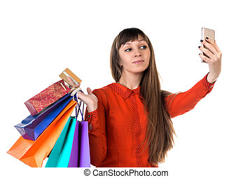 Young woman shops with credit card holding packages doing selfie